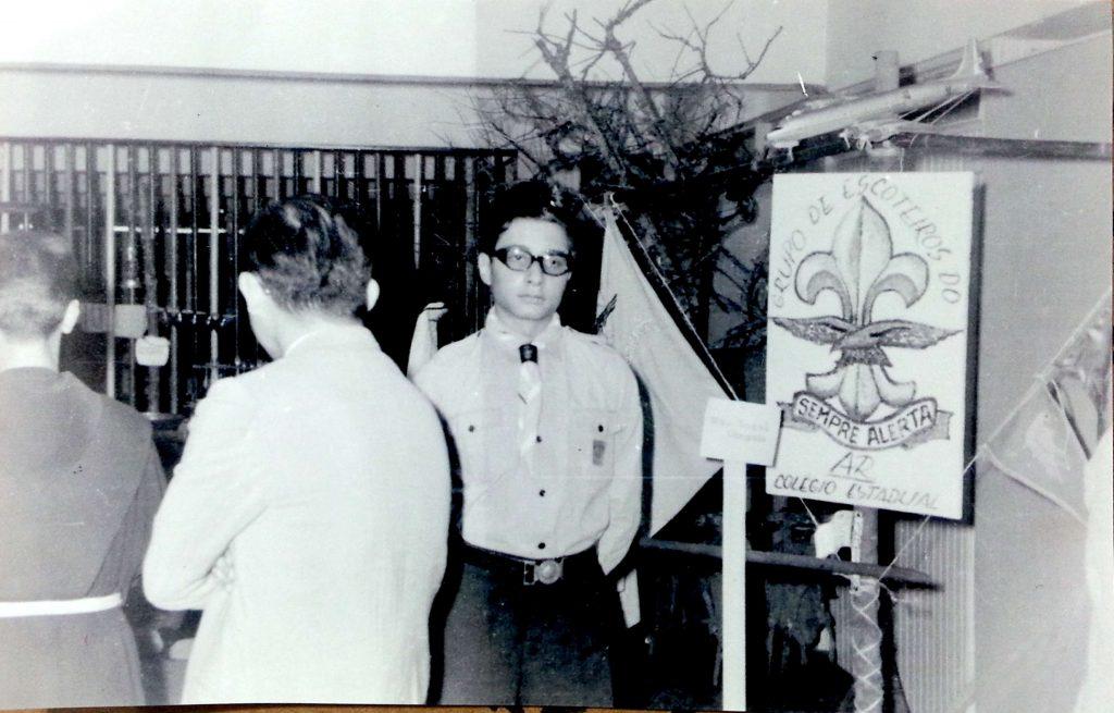 Ao centro Wilton Kuster parado ao lado da placa que possui escrito: Grupo de Escoteiros do Ar Santos Dumont e a Flor de Liz desenhada no meio.